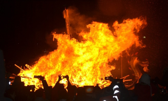 The galley burns as the crowd looks on