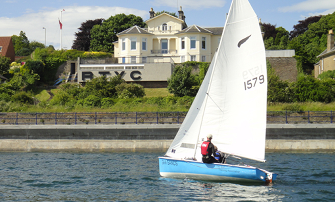 A Kestrel class of boat passing the clubhouse