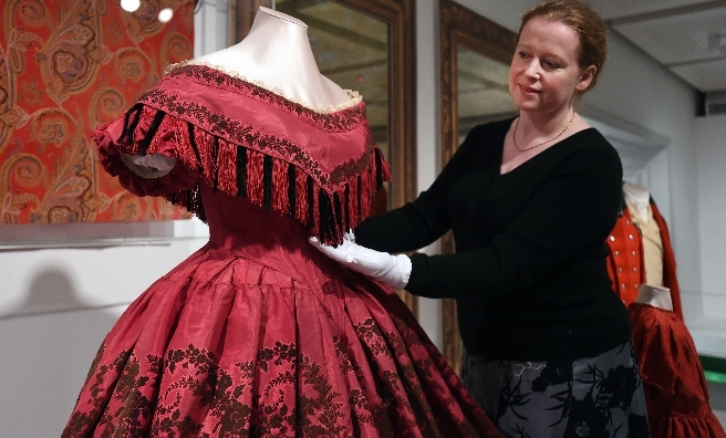 Rebecca Quinton, Curator of European Costume and Textiles at Glasgow Museums with an evening dress circa 1860. Photo copyright CSG CIC Glasgow Museums Collection