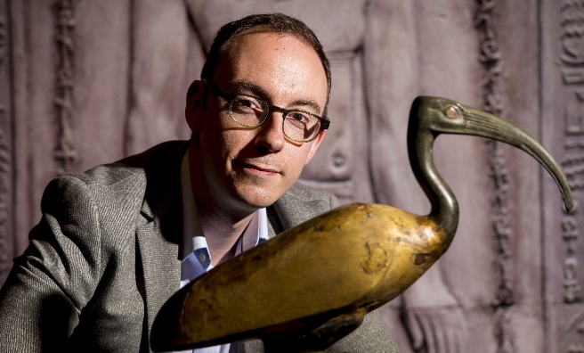 Dr Campbell Price, Curator of Egypt and Sudan, Manchester Museum with a beautiful gilded ibis, one of the exhibits on display at Kelvingrove Museum