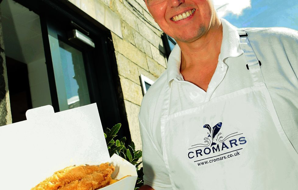 Colin Cromar stands proudly outside his fish shop, Cromars, St Andrews. Pic: John Stevenson. Courier.