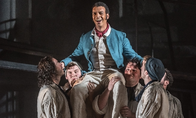 Roderick Williams as Billy Budd with members of the Chorus of Opera North in Opera North's BILLY BUDD by Britten. © CLIVE BARDA/ ArenaPAL
