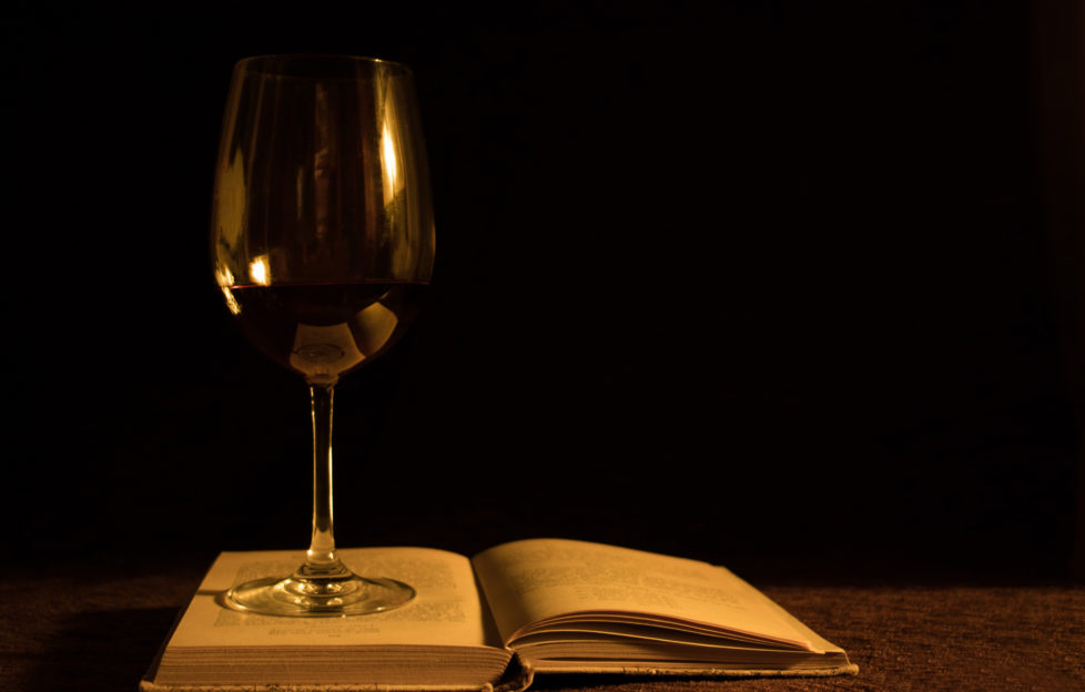 A wine glass and a book