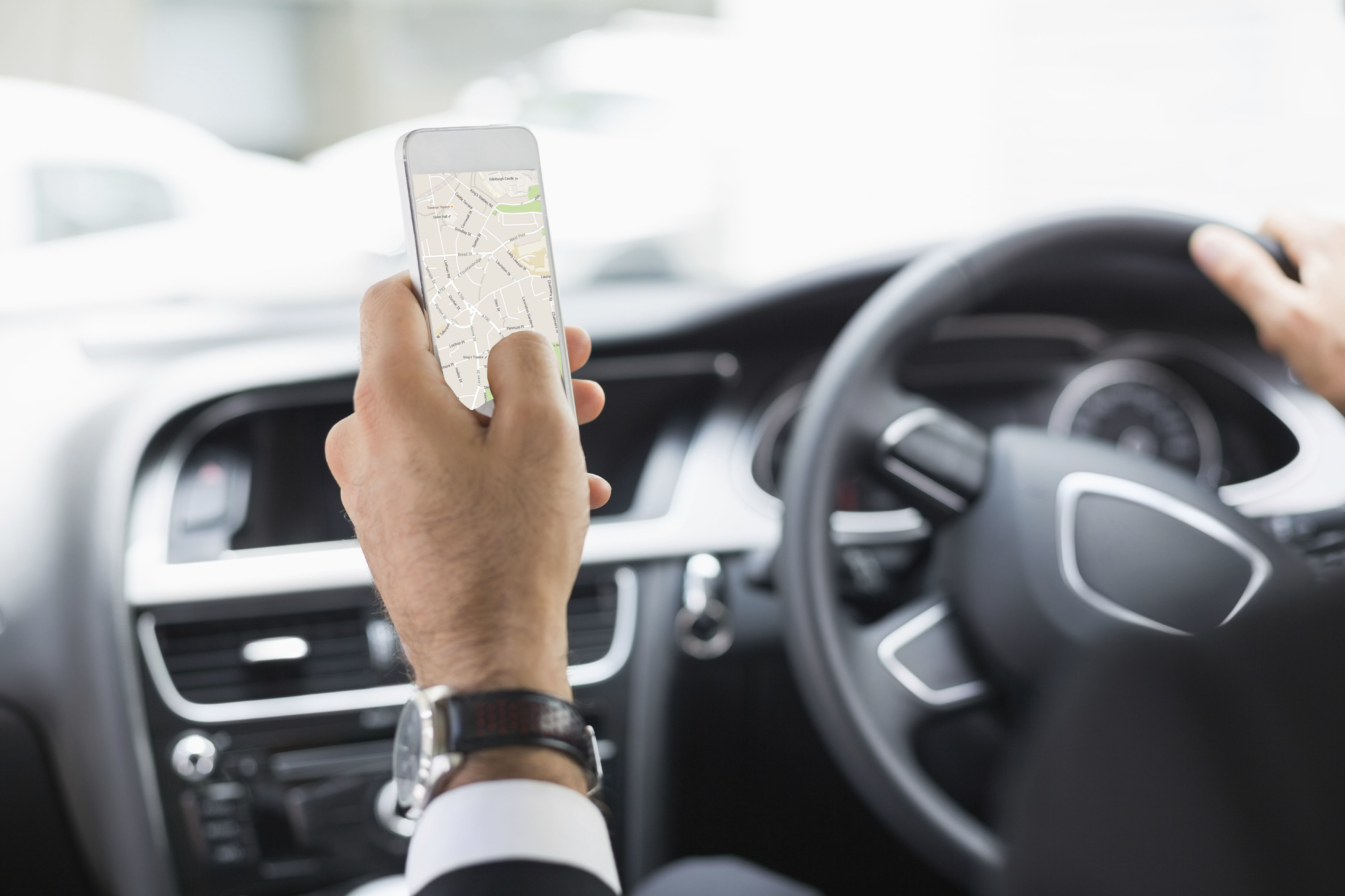 Man holding smartphone while driving