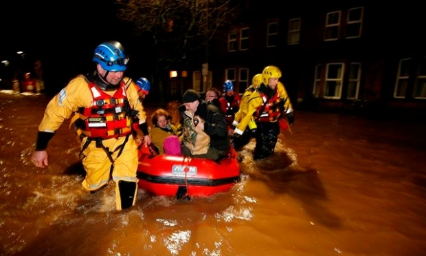 A team of rescue workers guides a boatload of residents to safety at the height of Storm Desmond last week (PA Images)