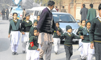 A plainclothes security officer escorts students rescued from nearby school during a Taliban attack in Peshawar, Pakistan.