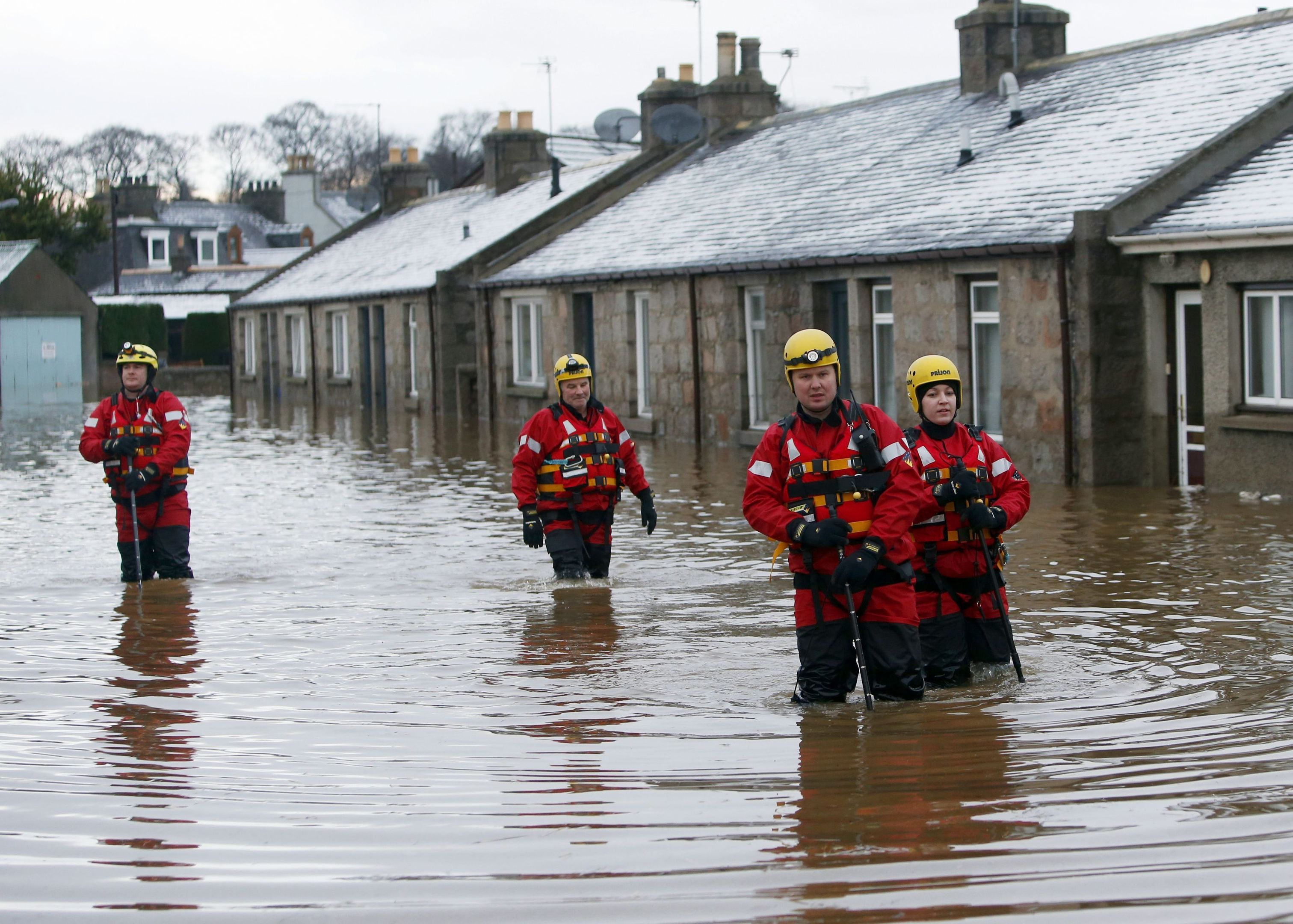 Members of the emergency services wade along Canal Road in Port Elphinstone (Danny Lawson/PA Wire)