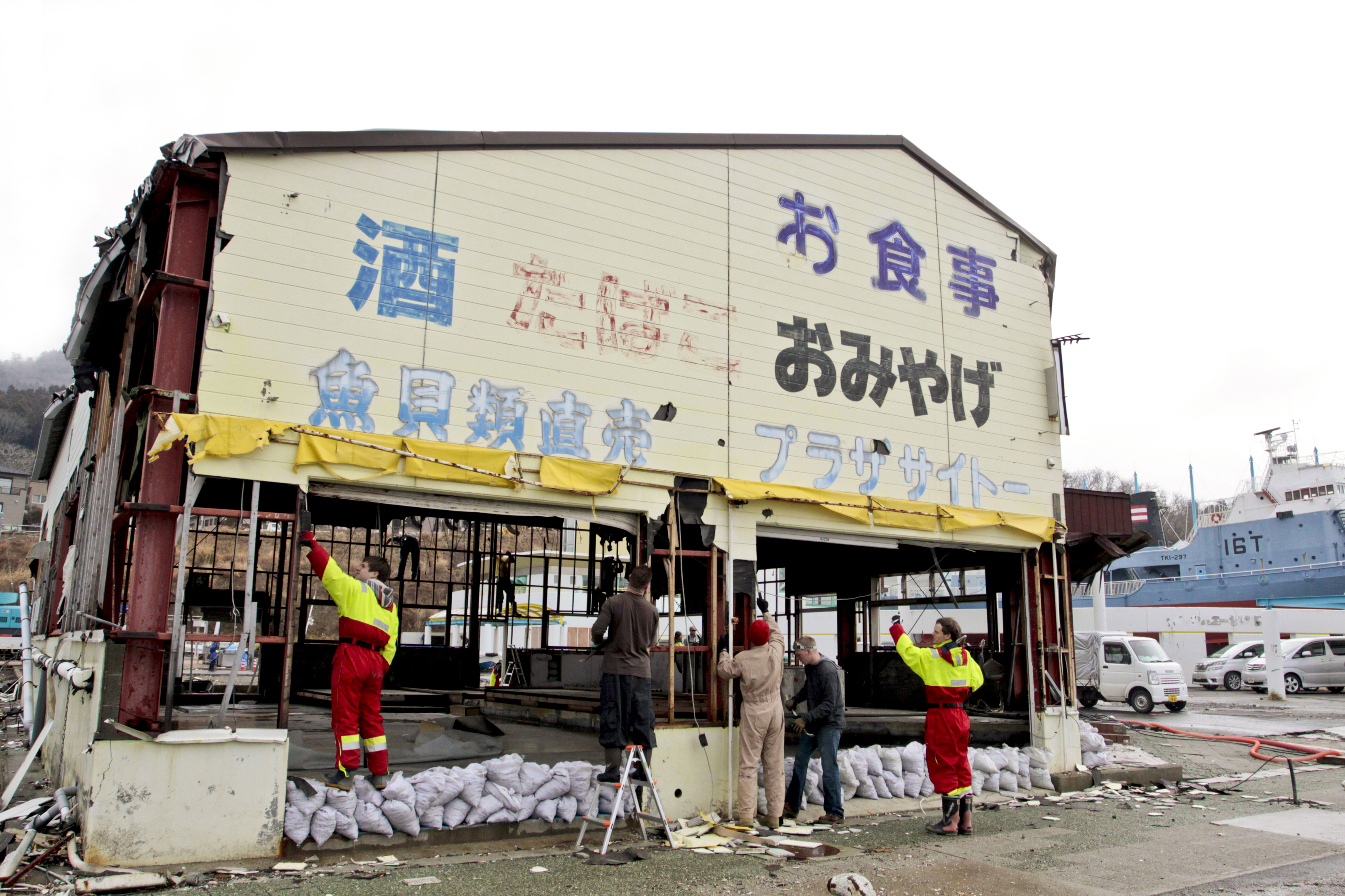 Volunteers remove old walls of what used to be a local souvenir shop and restaurant at a dock in Ishinomaki, Japan (U.S. Marine Corps photo by Lance Cpl. Benjamin Pryer)