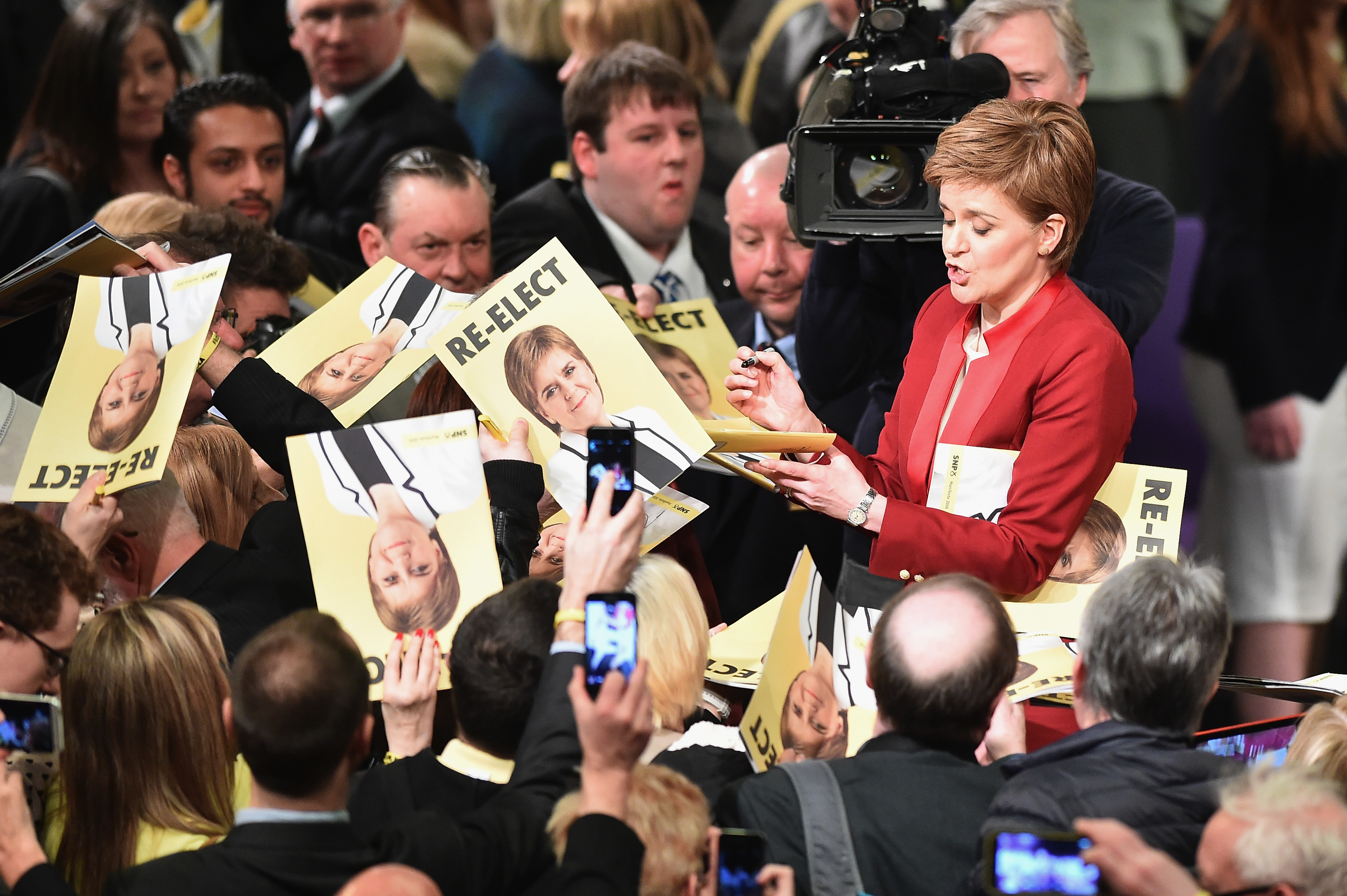 SNP leader Nicola Sturgeon signs copies of the party manifesto at the launch in Edinburgh (Jeff J Mitchell/Getty Images)
