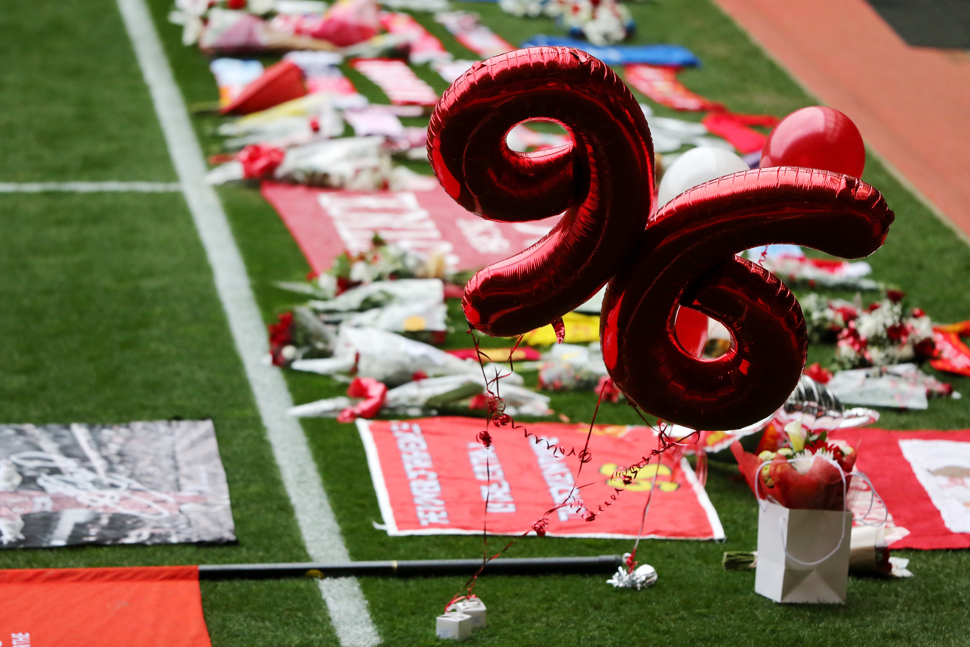 Tributes are placed on the pitch before the memorial service (Christopher Furlong/Getty Images)
