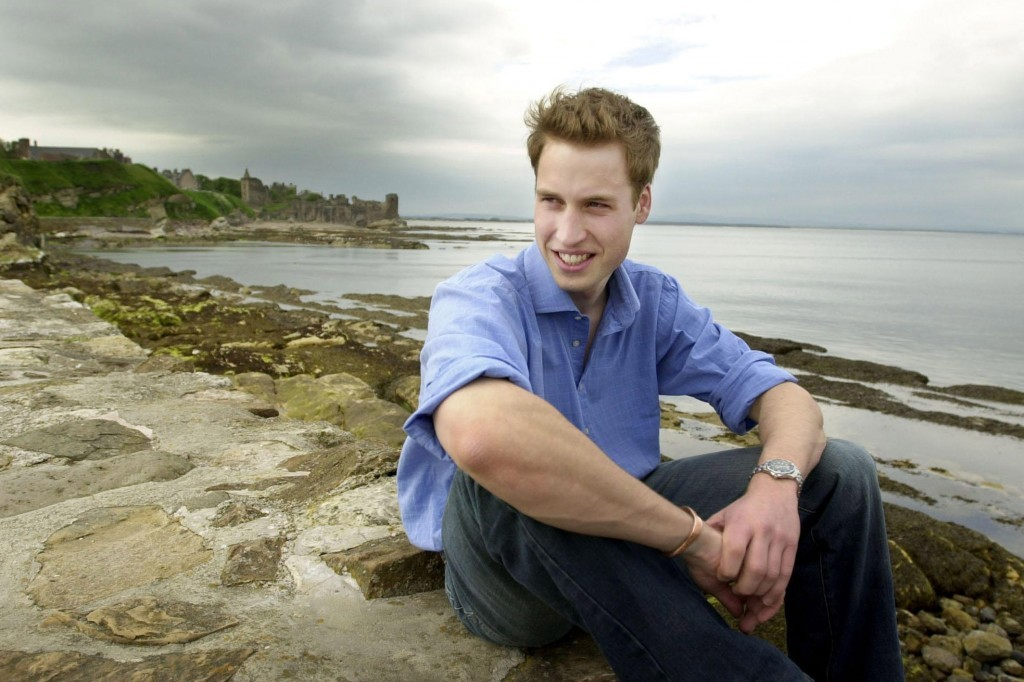 Prince William sits by the sea at St Andrews, with the castle in the background, during his uni days (PA Archive)