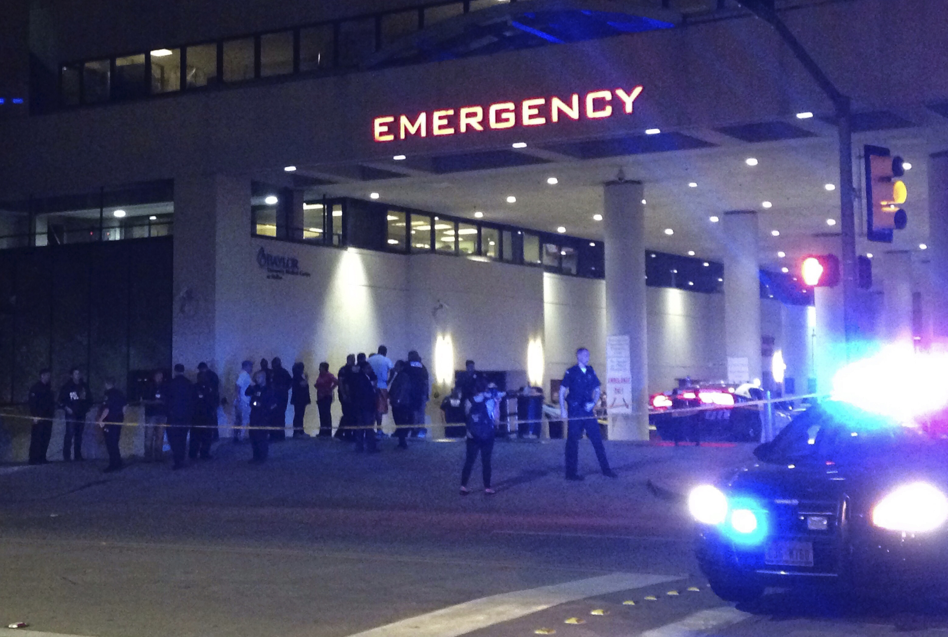 Police and others gather at the emergency entrance to Baylor Medical Center in Dallas, where several police officers were taken after shootings Thursday, July 7, 2016.. (AP Photo/Emily Schmall)