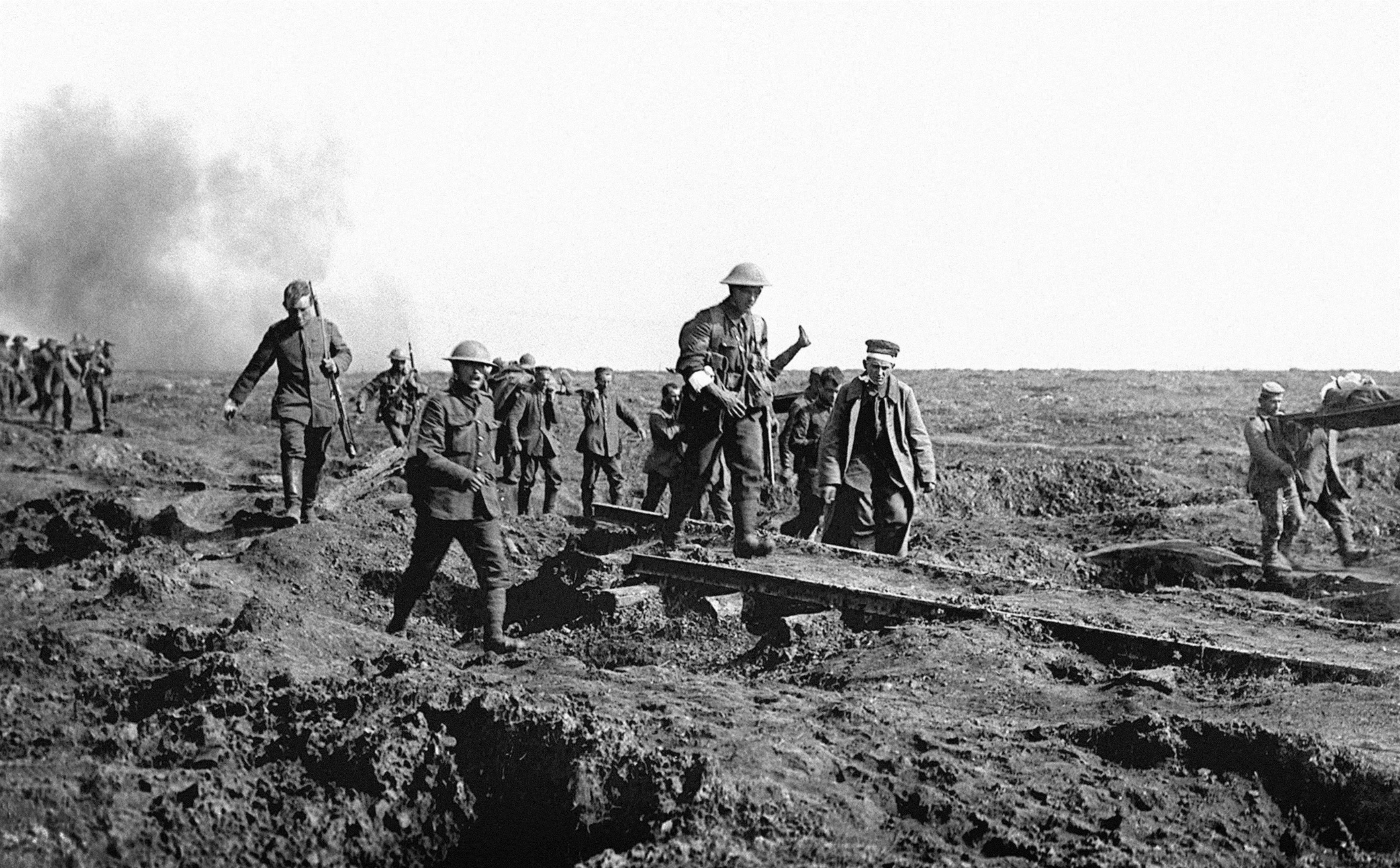 German prisoners help to carry British wounded back to their trenches (PA Archive)