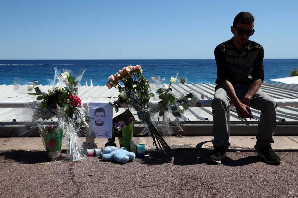 A man sits next to flowers and tributes  on the Promenade des Anglais   (Carl Court/Getty Images)