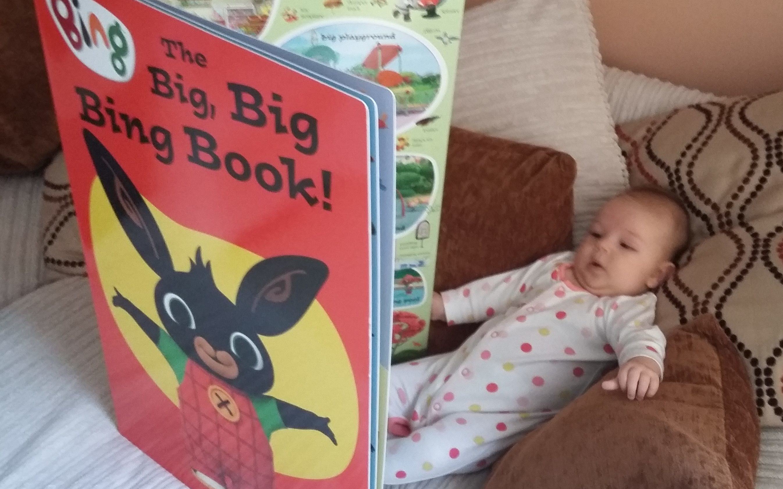 12 weeks old and already our Genius Child likes relaxing in the chair and a reading a big book