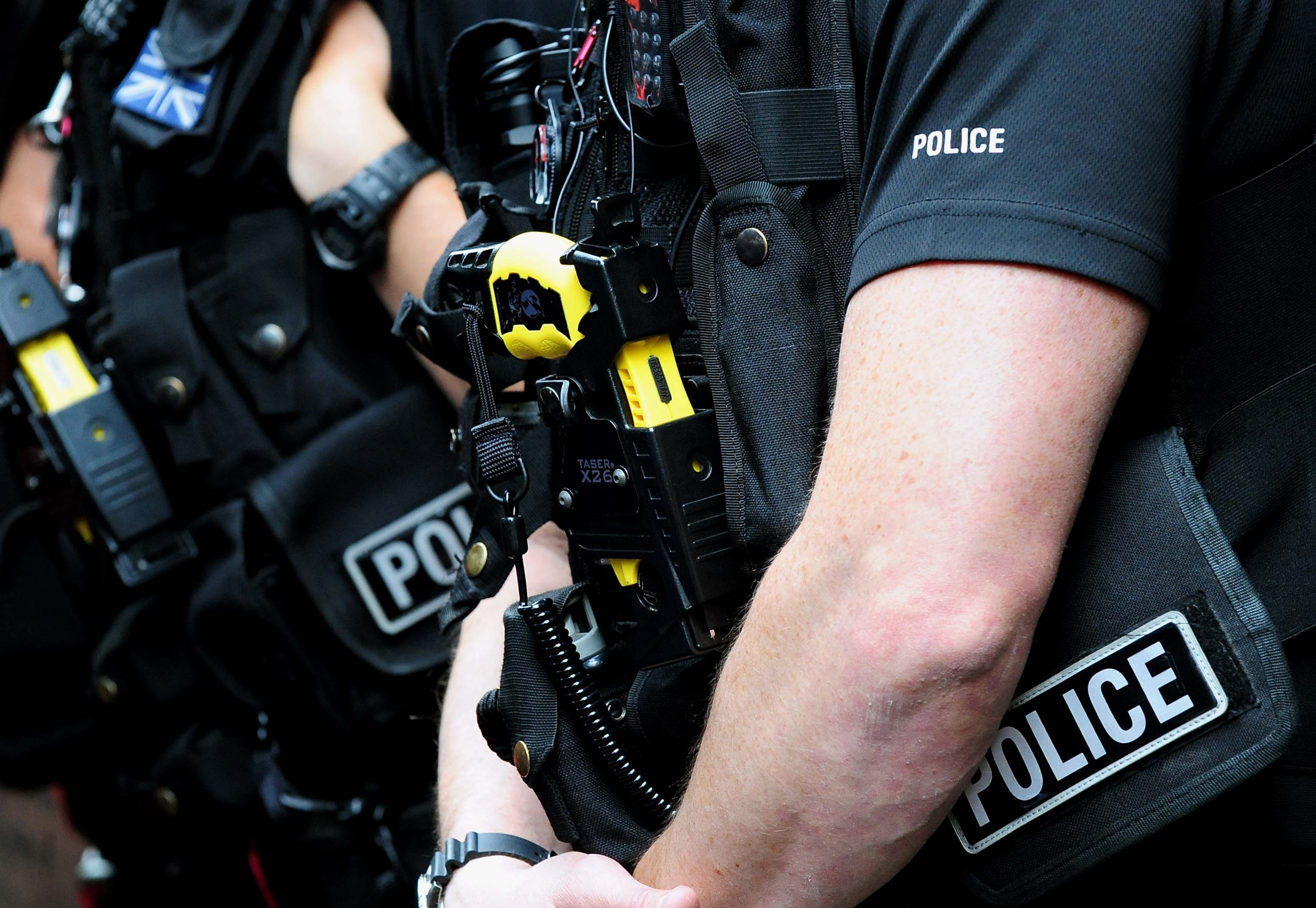Police officers carrying Tasers (PA Archive)