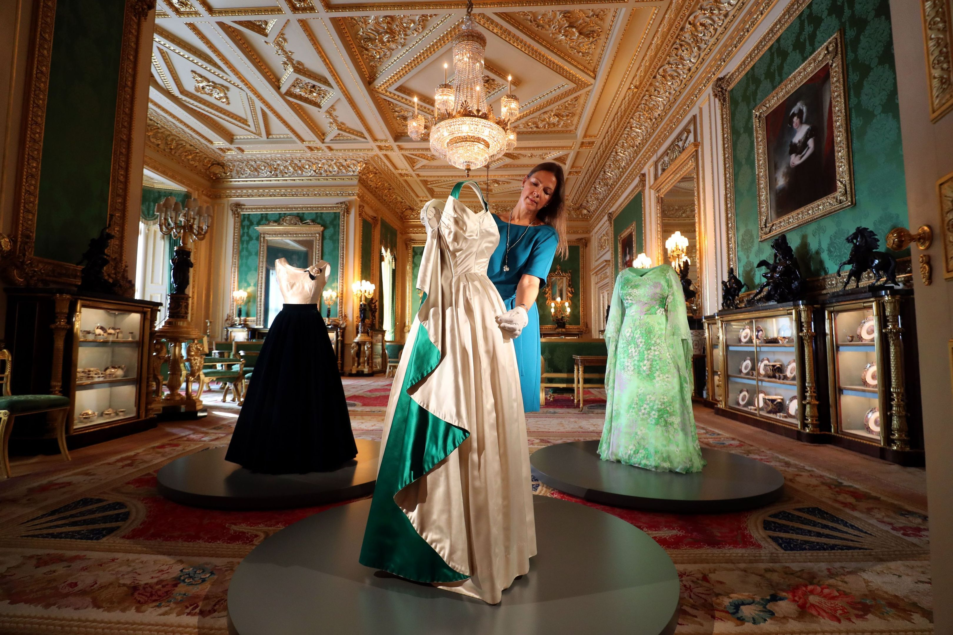 Curator Caroline de Guitaut arranges an evening gown worn by The Queen, in the Green Drawing Room (Steve Parsons/PA Wire)