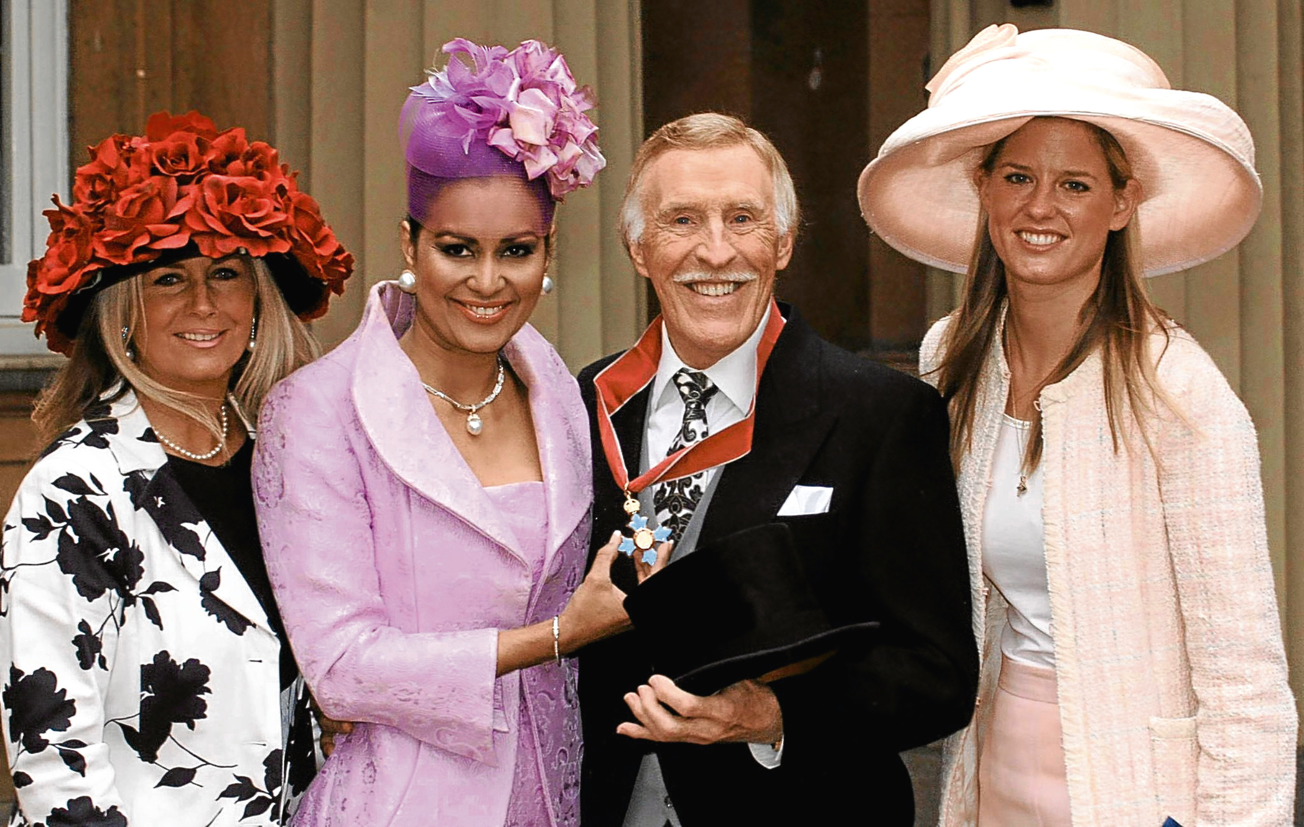 Bruce Forsyth with his wife Wilnelia and daughters Julie Purdie (left) and Louisa Monro (right) at Buckingham Palace