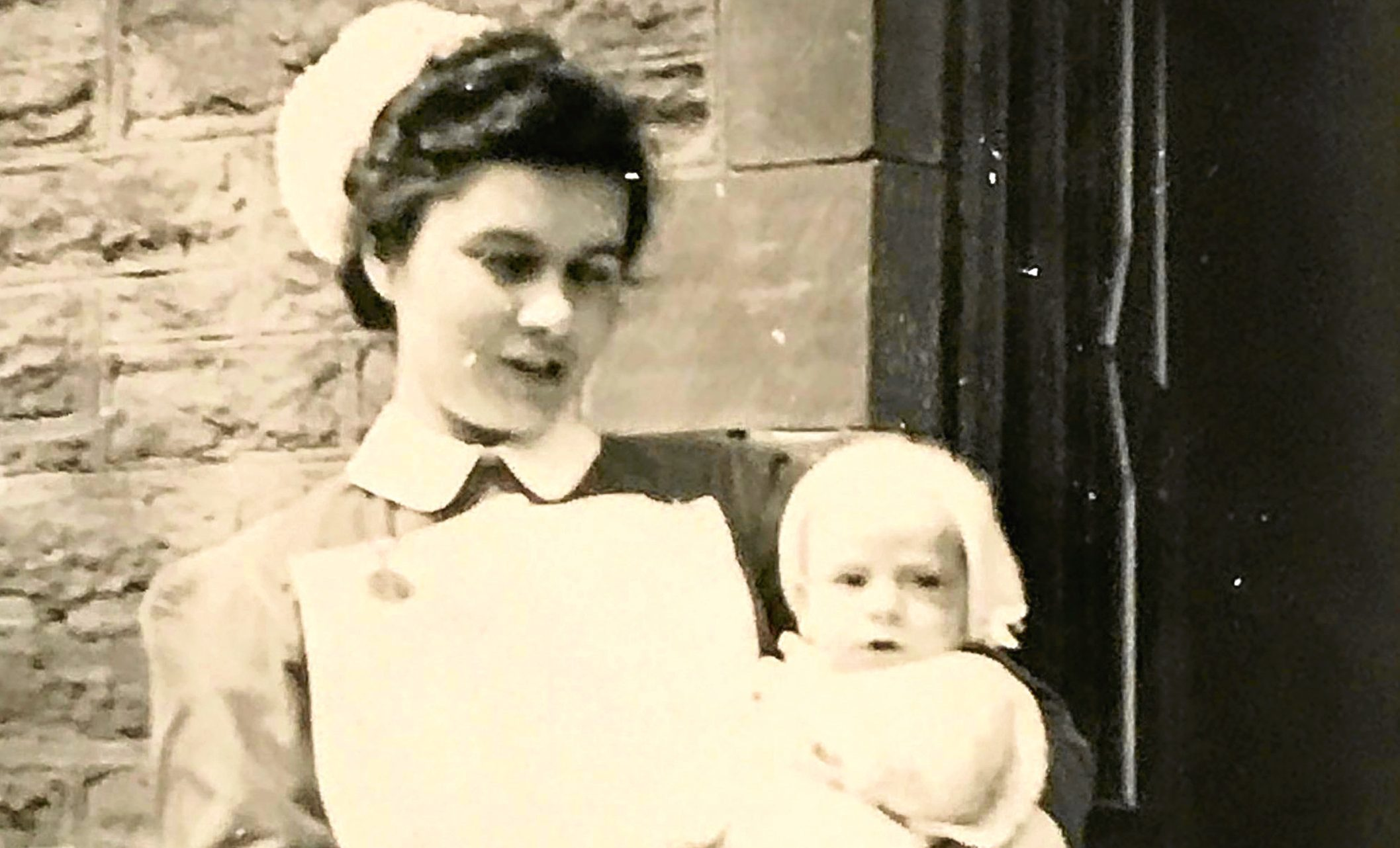 Margaret McInroy, nee Ansell, when she was a nurse with baby Bill Douglas