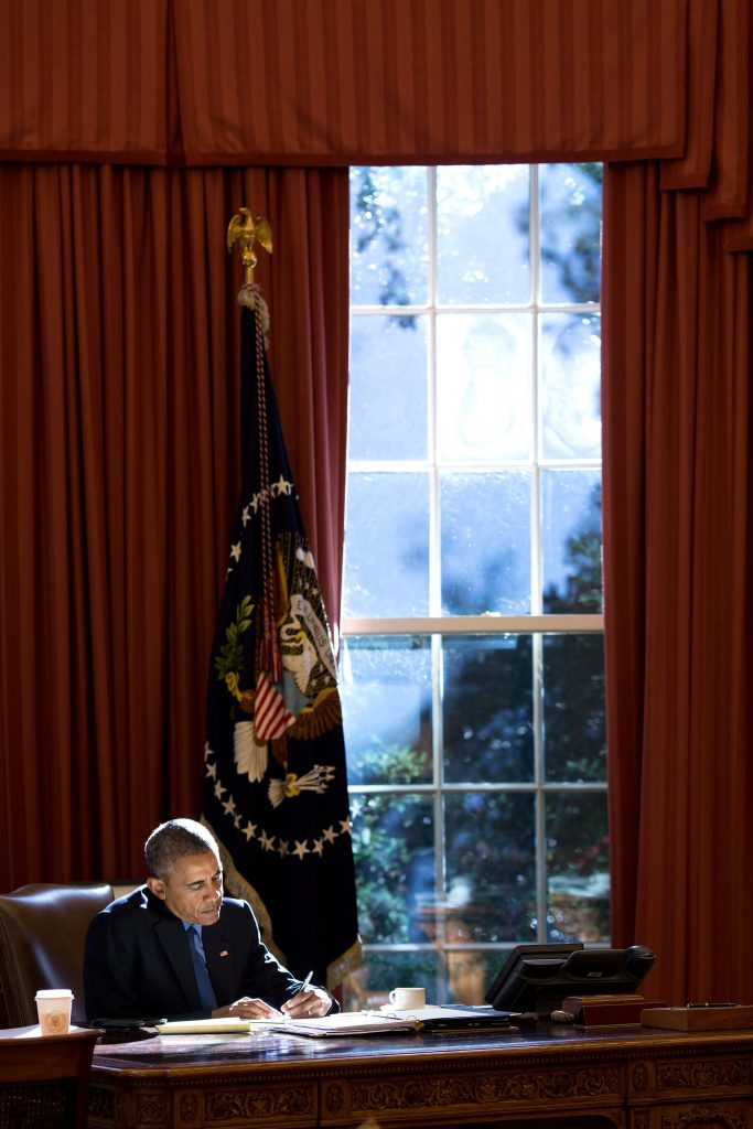 """Oct. 23, 2015 """"Afternoon autumn light bathes the President as he works at the Resolute Desk in the Oval Office."""" (Official White House Photo by Pete Souza)"""