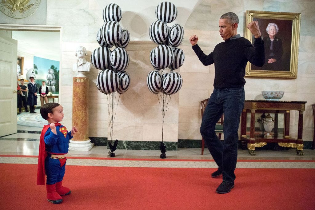 """Oct. 31, 2016 """"The President was about to welcome local children for Halloween trick-or-treating when he ran into Superman Walker Earnest, son of Press Secretary Josh Earnest, in the Ground Floor Corridor of the White House. 'Flex those muscles,' he said to Walker."""" (Official White House Photo by Pete Souza)"""