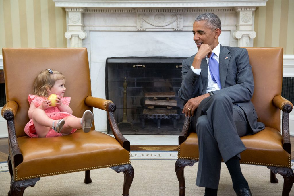 """June 22, 2016 """"The great thing about children is you just don't know what they will do in the presence of the President. So when David Axelrod stopped by the Oval Office with one of his sons' family, Axe's granddaughter, Maelin, crawled onto the Vice President's seat while the President continued his conversation with the adults. Then at one point, Maelin glanced over just as the President was looking back at her."""" (Official White House Photo by Pete Souza)"""