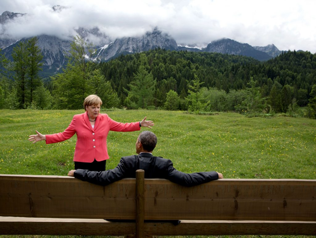 """June 8, 2015 """"We were at the G7 Summit in Krün, Germany. Chancellor Angela Merkel asked the leaders and outreach guests to make their way to a bench for a group photograph. The President happened to sit down first, followed closely by the Chancellor. I only had time to make a couple of frames before the background was cluttered with other people."""" (Official White House Photo by Pete Souza)"""