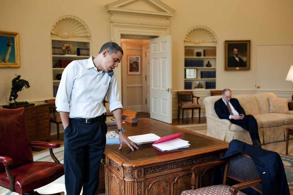 President Barack Obama talks to a Member of Congress on the phone in the Oval Office, March 21, 2010. Assistant to the President for Legislative Affairs Phil Schiliro works in the background. (Official White House Photo by Pete Souza) This official White House photograph is being made available only for publication by news organizations and/or for personal use printing by the subject(s) of the photograph. The photograph may not be manipulated in any way and may not be used in commercial or political materials, advertisements, emails, products, promotions that in any way suggests approval or endorsement of the President, the First Family, or the White House.