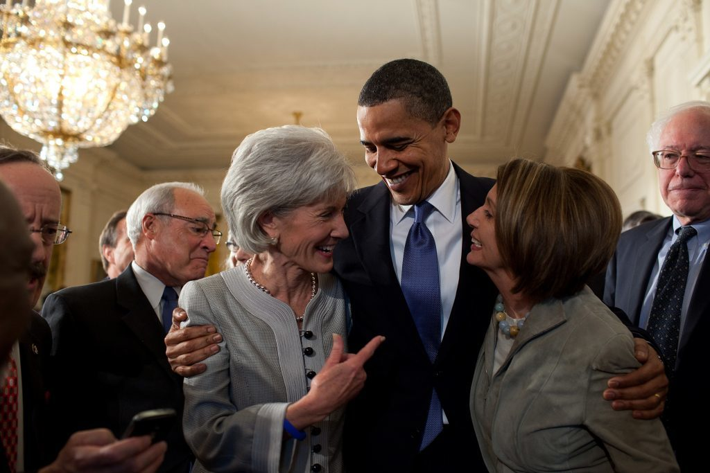 President Barack Obama embraces Secretary of Health and Human Services Kathleen Sebelius, left, and House Speaker Nancy Pelosi after signing the health insurance reform bill in the East Room of the White House, March 23, 2010. (Official White House Photo by Pete Souza) This official White House photograph is being made available only for publication by news organizations and/or for personal use printing by the subject(s) of the photograph. The photograph may not be manipulated in any way and may not be used in commercial or political materials, advertisements, emails, products, promotions that in any way suggests approval or endorsement of the President, the First Family, or the White House.