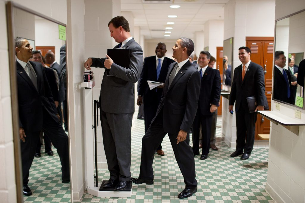 President Barack Obama puts his toe on the scale as Trip Director Marvin Nicholson tries to weigh himself during a hold in the volleyball locker room at the University of Texas in Austin, Texas, Aug. 9, 2010. (Official White House Photo by Pete Souza)