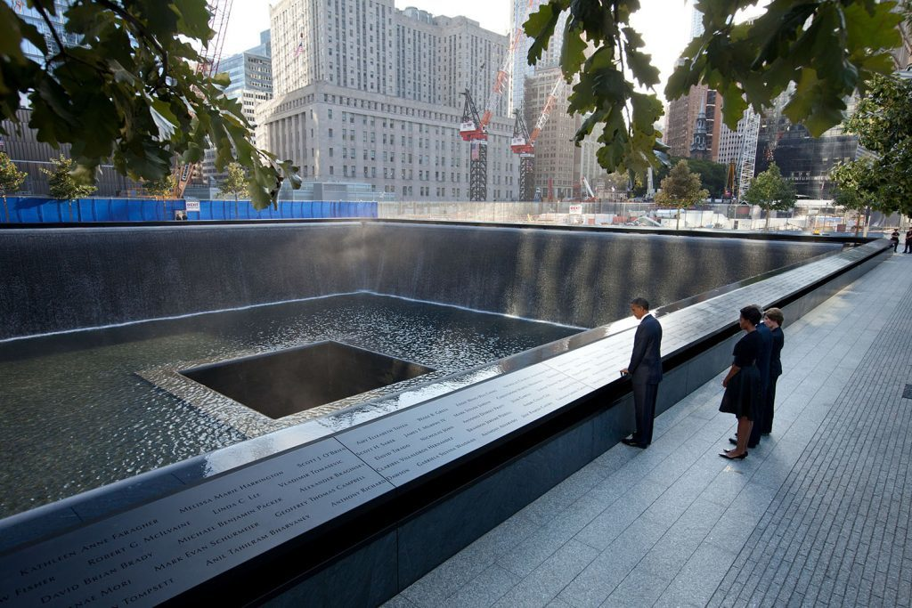 """Sept. 11, 2011 """"Chuck Kennedy captured this scene with a remote camera as the President and First Lady, along with former President George W. Bush and former First Lady Laura Bush, paused at the North Memorial Pool of the National September 11 Memorial in New York City. The North Memorial pool sits in the footprint of the north tower, formerly 1 World Trade Center."""" (Official White House Photo by Chuck Kennedy) This official White House photograph is being made available only for publication by news organizations and/or for personal use printing by the subject(s) of the photograph. The photograph may not be manipulated in any way and may not be used in commercial or political materials, advertisements, emails, products, promotions that in any way suggests approval or endorsement of the President, the First Family, or the White House."""