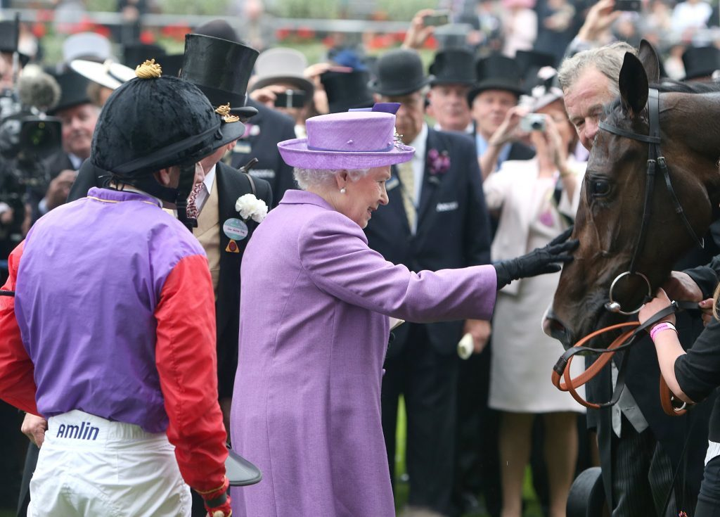 Queen Elizabeth II pats her horse Estimate after it won the Gold Cup ridden by jockey Ryan Moore (left) during Ladies' Day at Royal Ascot