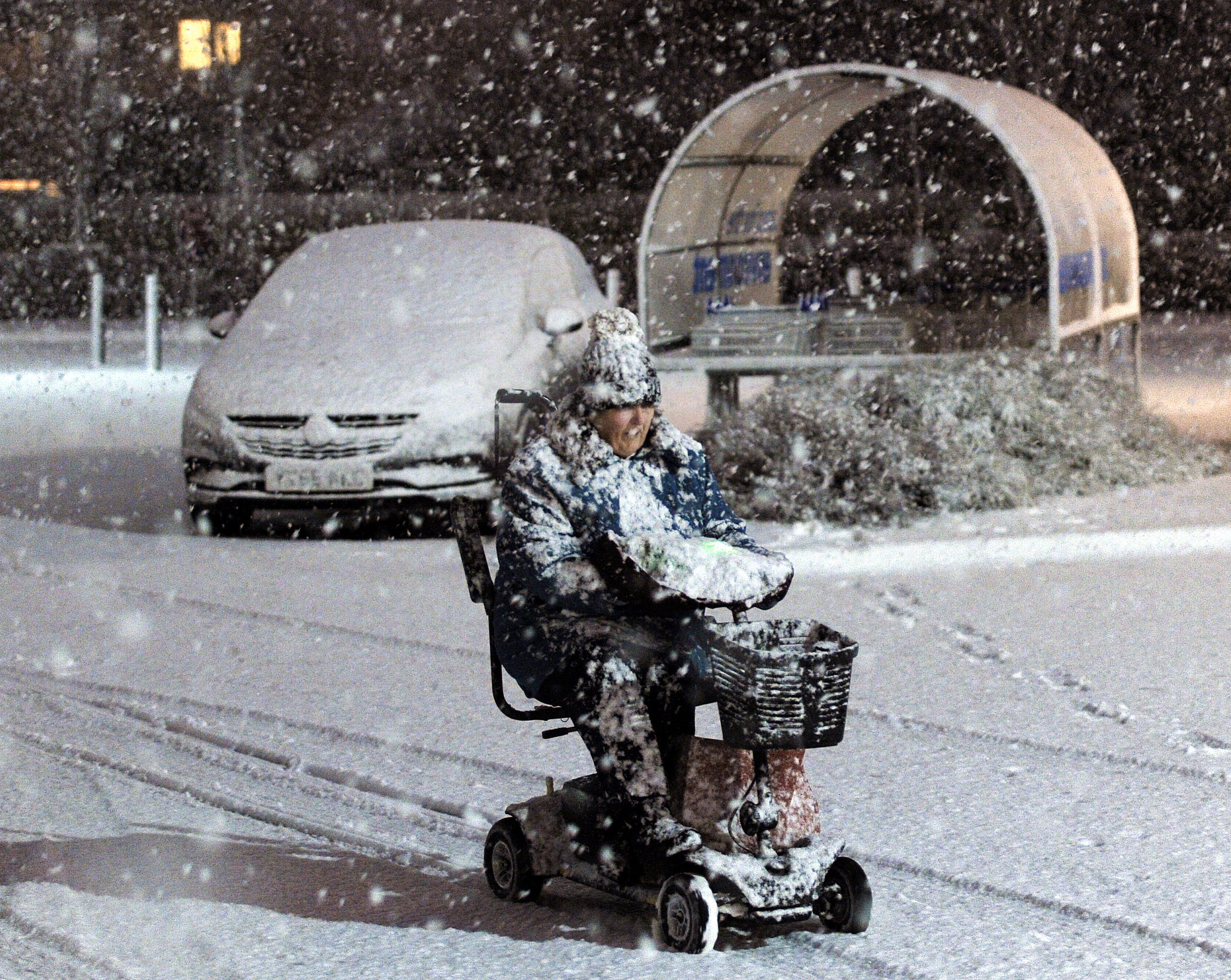 A lady makes her way through the snow on a mobility scooter in Filey on the East coast, as Scotland and the North of England were covered in a blanket of snow while the east coast was braced for a storm surge. (John Giles/PA Wire)