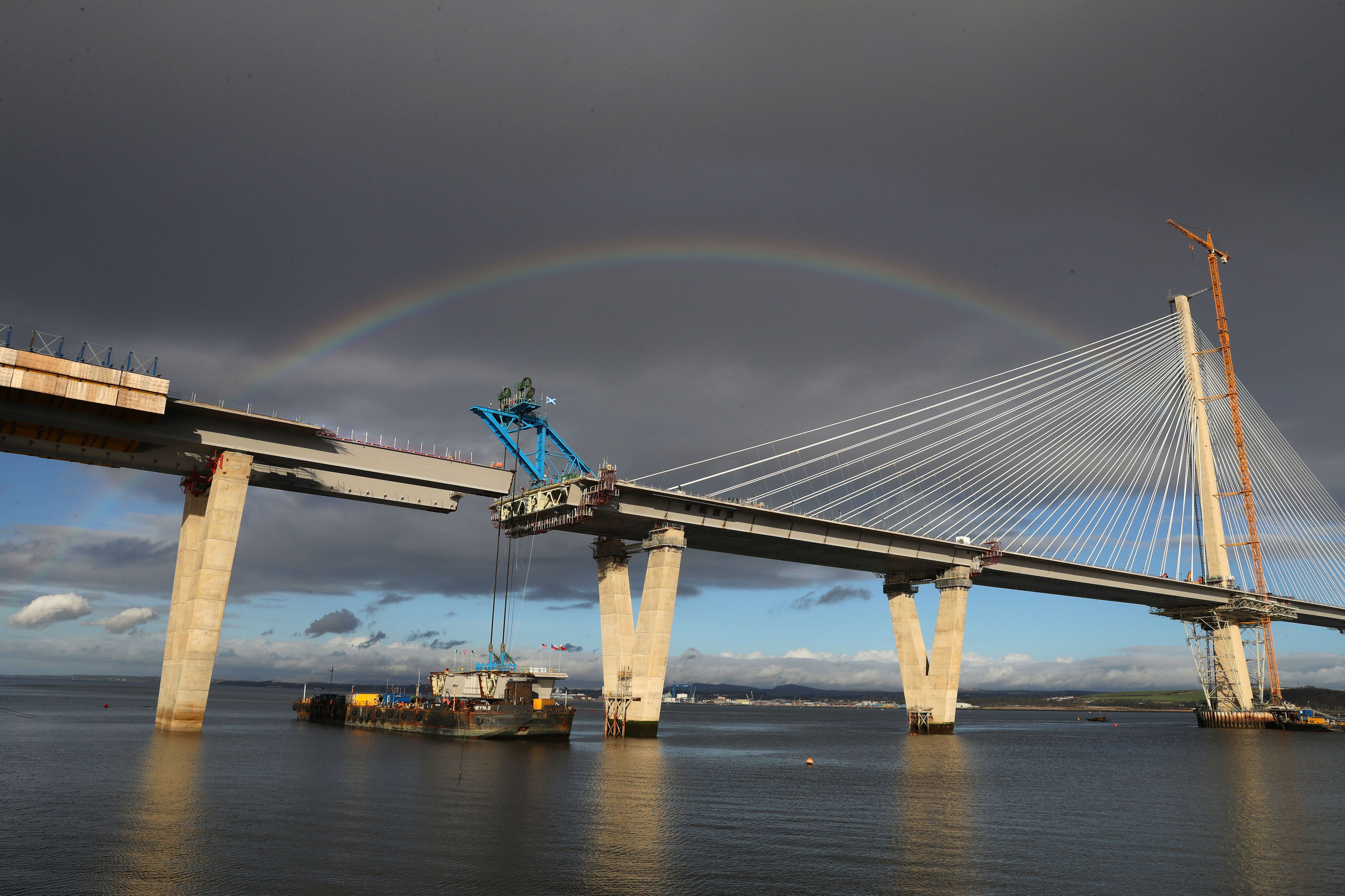 A rainbow is seen as cables are placed on a section of the new Queensferry Crossing bridge on a barge ready to lift into place (Andrew Milligan/PA Wire)