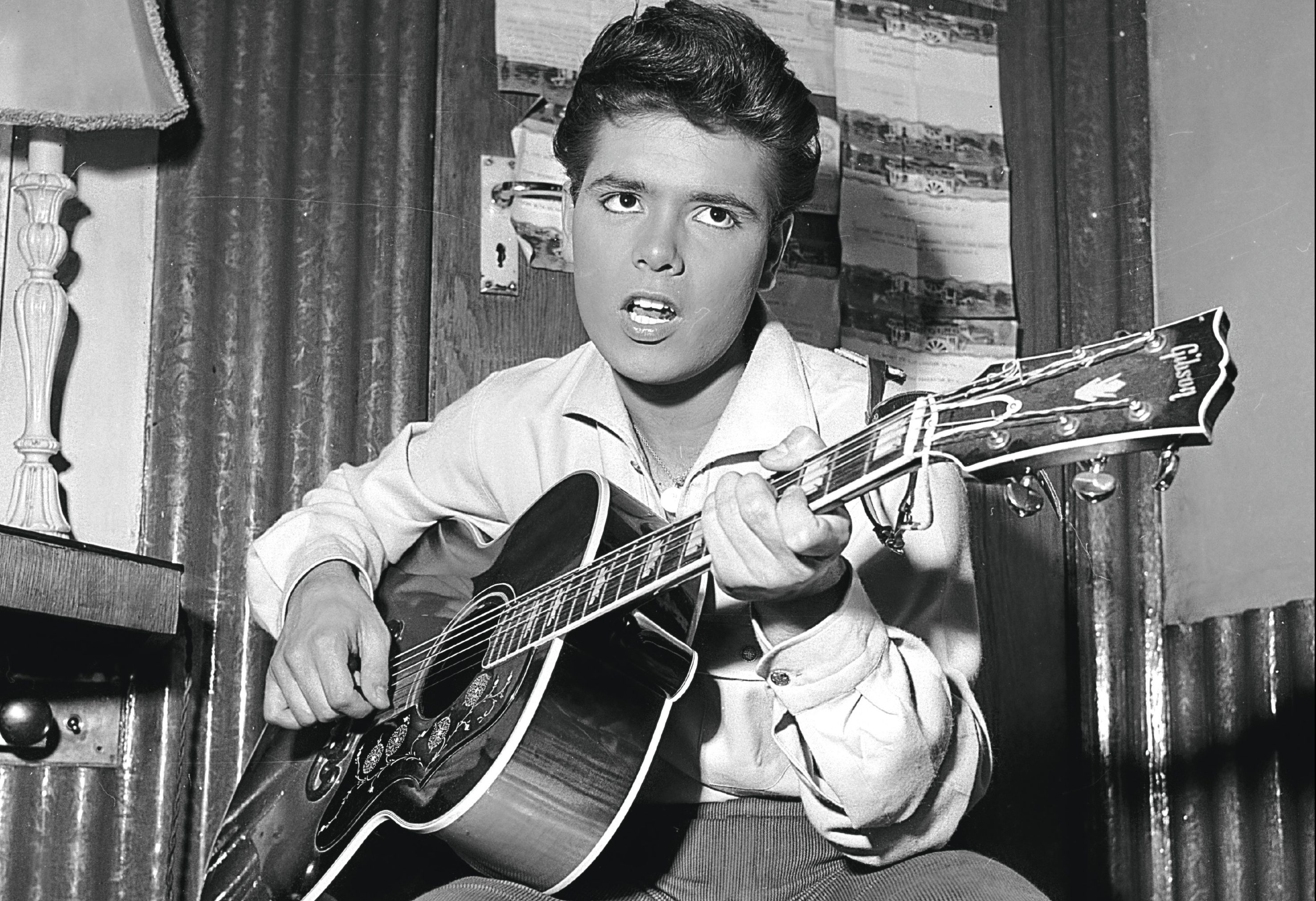 Cliff Richard strums a tune on his trusty guitar before a concert, 1960 (John Pratt/Keystone Features/Getty Images)