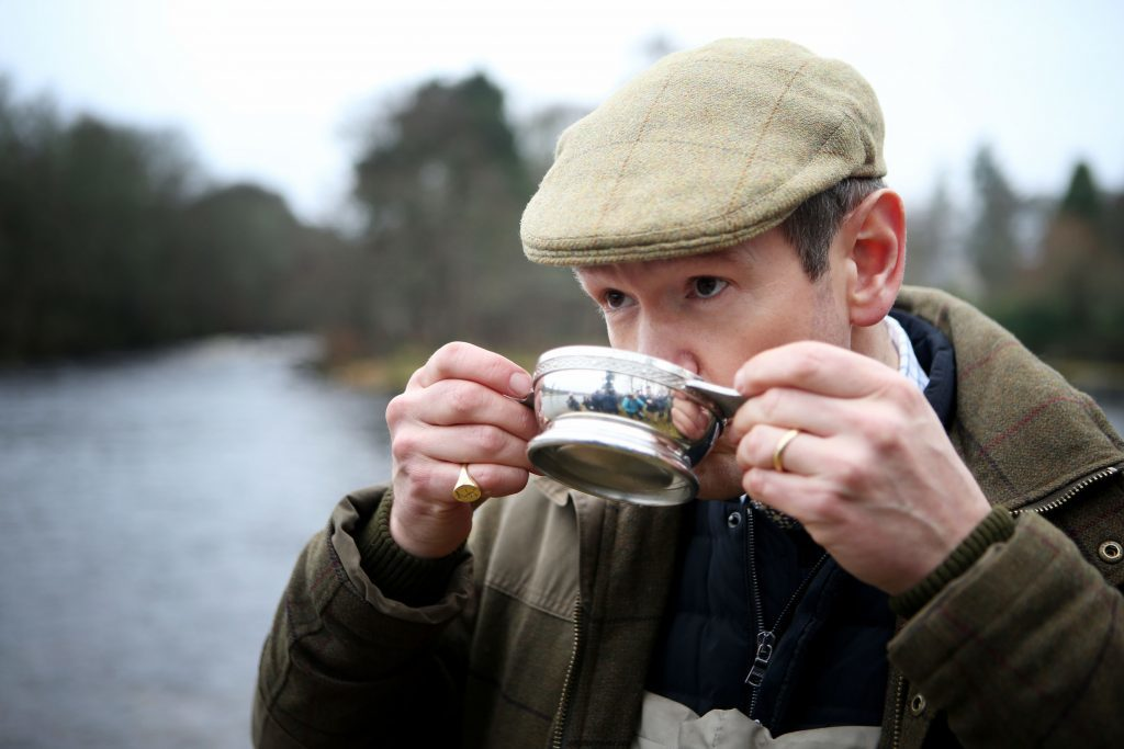 Armstrong drinks a dram of whisky from a quaich before making the first cast to officially open the new fishing season (Jane Barlow/PA Wire)
