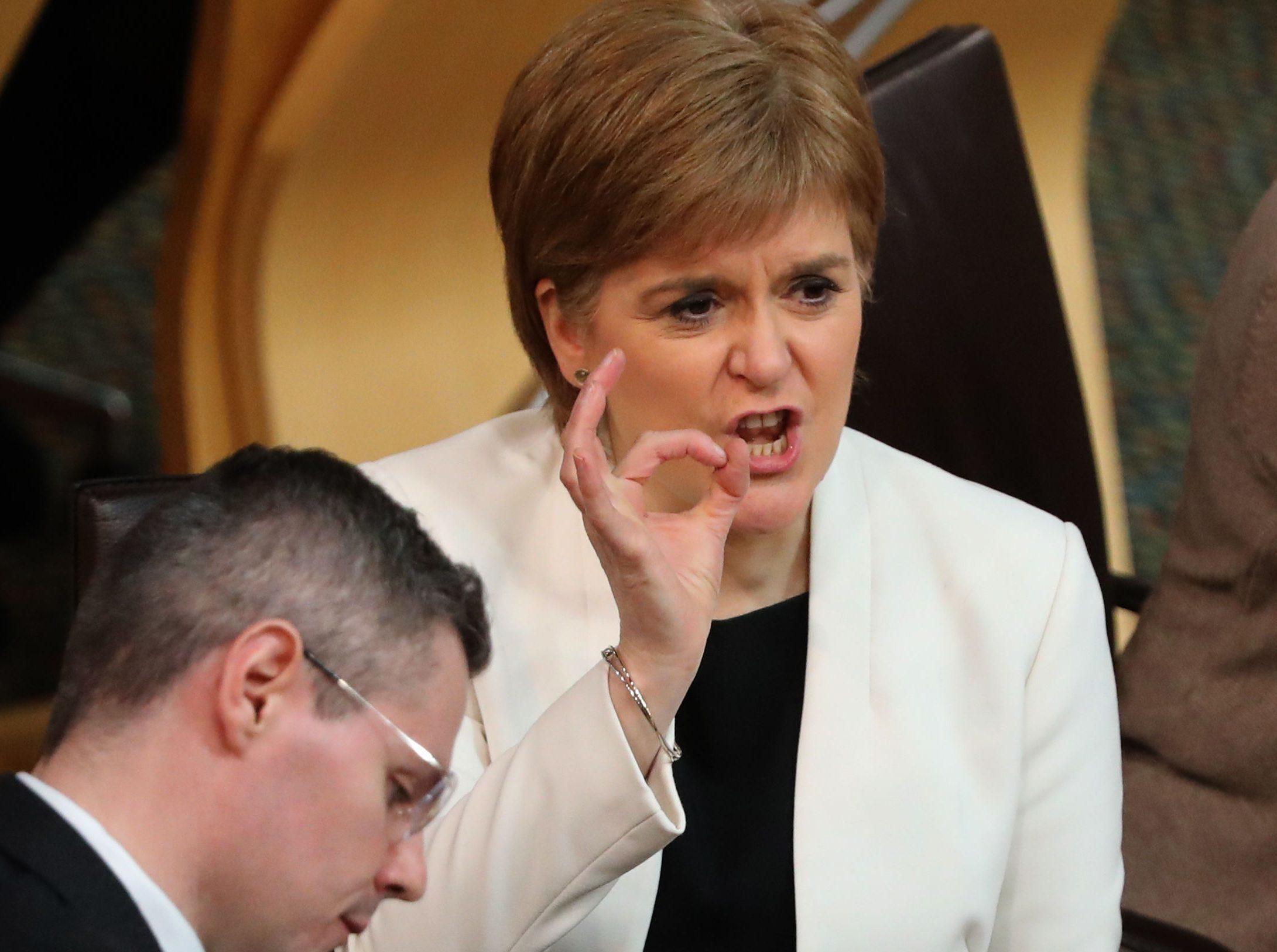 First Minister Nicola Sturgeon after Finance Secretary Derek Mackay's (left) speech during a Budget debate at the Scottish Parliament  (Andrew Milligan/PA Wire)
