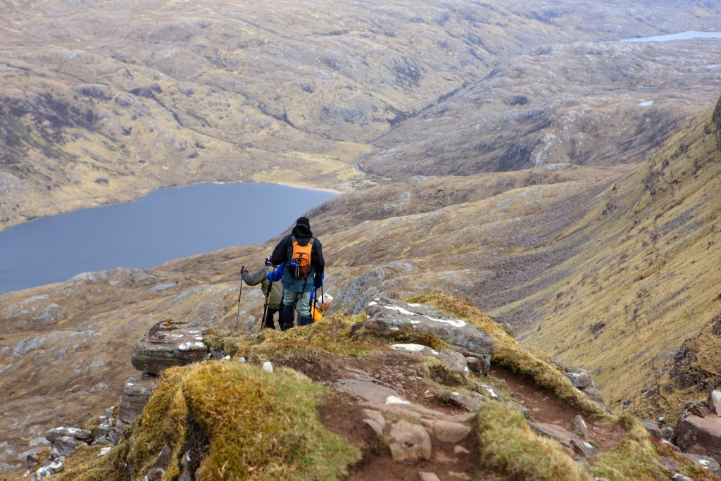 Men descending from Caisteal Liath the highest point on Suilven in the Scottish Highlands