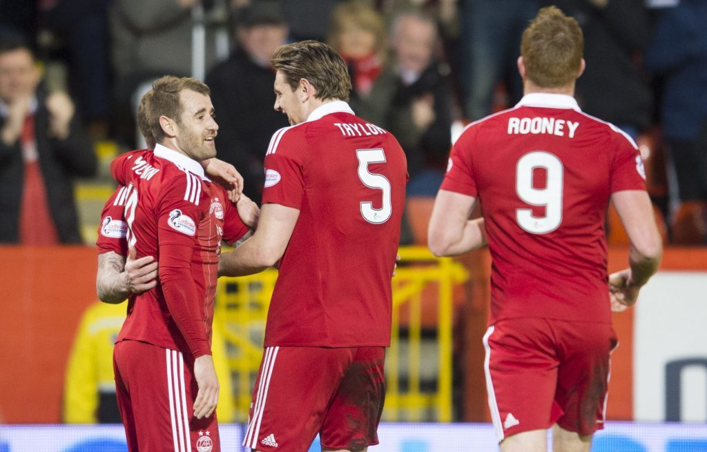 Aberdeen goalscorer Ash Taylor (centre) celebrates the opening goal with his team-mates (SNS Group / Bill Murray)