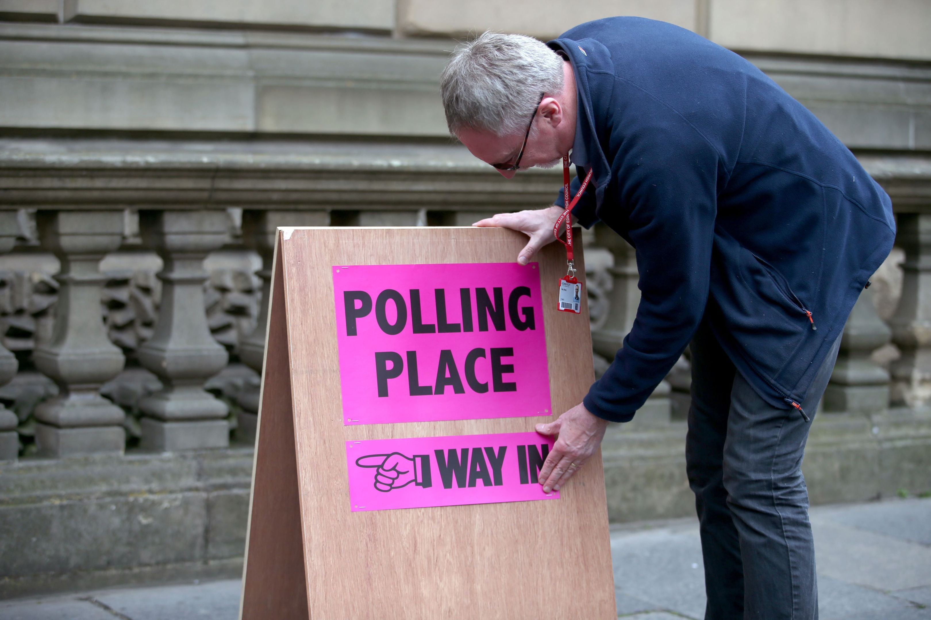 Polling logistics officer Roy Drury secures a polling station sign from Lothian Chambers in Edinburgh (Jane Barlow/PA Wire)