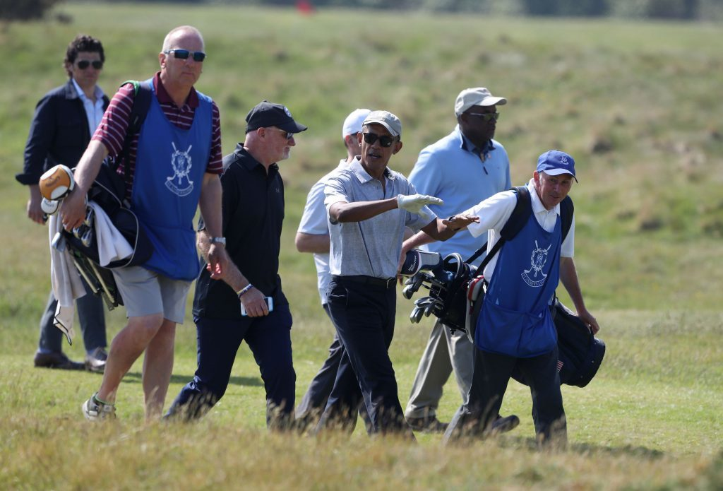 Former US president Barack Obama speaks with Sir Tom Hunter (black hat) as they move to the next hole (Andrew Milligan/PA Wire)