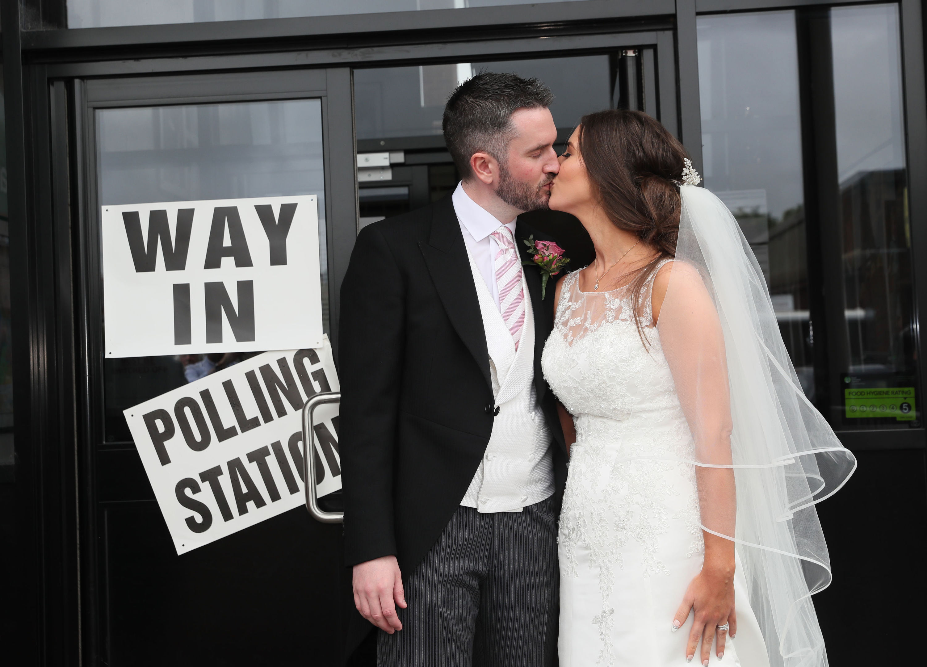 Alliance candidate for West Belfast Sorcha Eastwood casts her vote in the 2017 General Election, with her husband, Dale Shirlow, at a polling station in Lisburn, Northern Ireland, still wearing her wedding dress after they were married earlier in the day. (Brian Lawless/PA Wire)