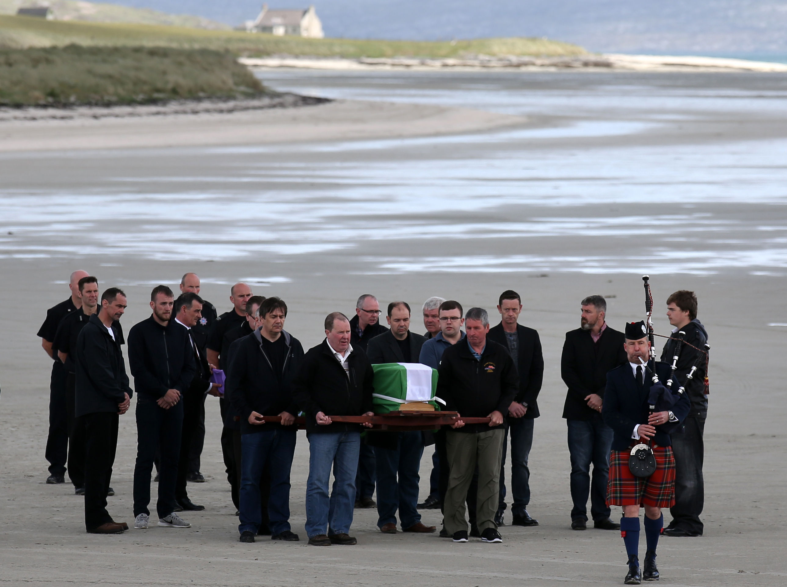 The coffin of Eilidh MacLeod draped in the Barra flag is carried across Traigh Mhor beach at Barra airport after it arrived by chartered plane. (Andrew Milligan/PA Wire)