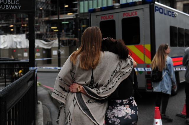 Two women hug as they walk near the scene of Saturday's terror attack (David Mirzoeff/PA)