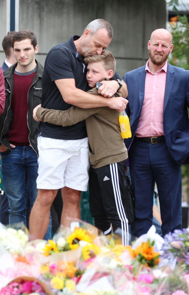 A man hugs his son after laying flowers near London Bridge (Isabel Infantes/PA)