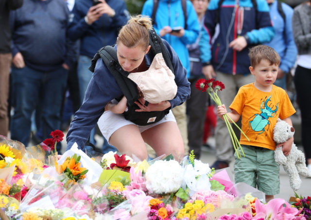 A mother lays flowers with her children near London Bridge (Isabel Infantes/PA)