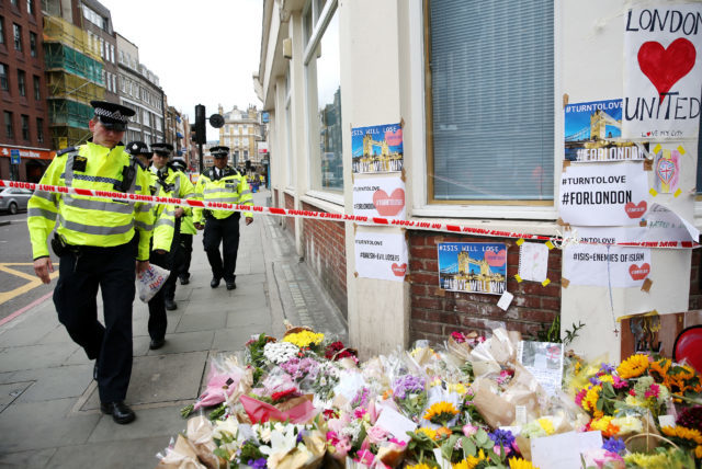 Police walk past flowers left out for the victims of Saturday's attack (Isabel Infantes/PA)
