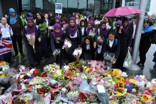 School girls leave flowers at a vigil in Potters Fields Park, central London (Nick Ansell/PA)
