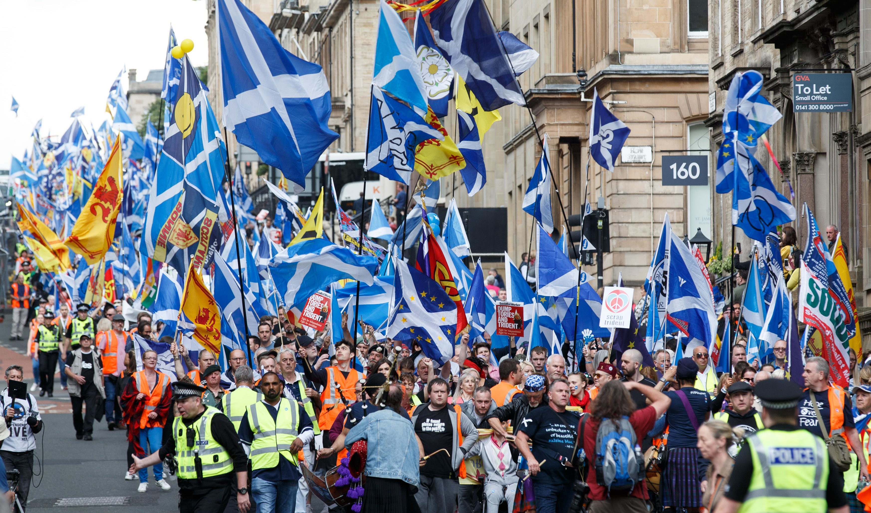 People taking part in the March for Independence wave Saltires as they head through Glasgow city centre (Robert Perry/PA Wire)