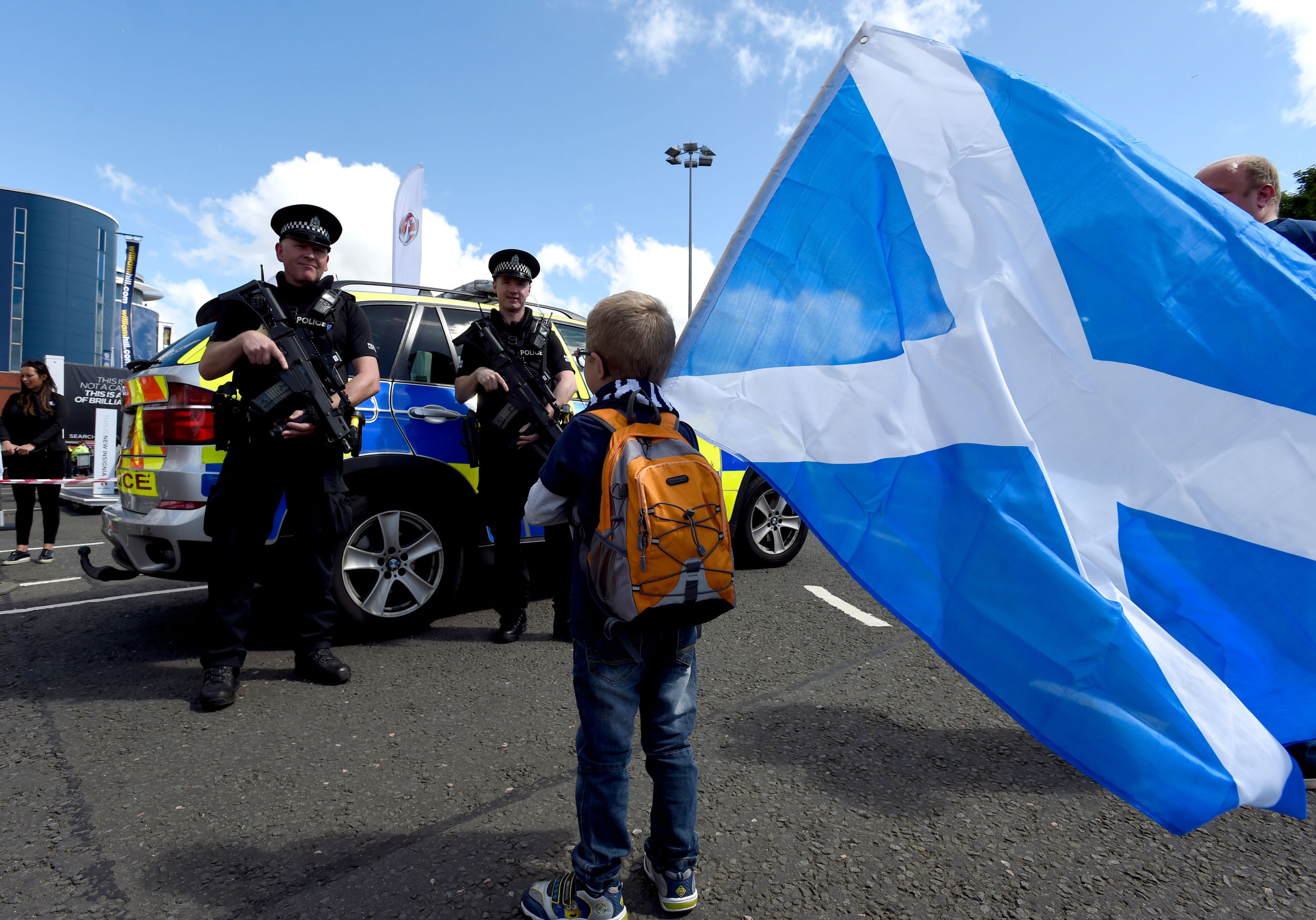 Armed police near a young fan holding a Scotland flag outside the ground ahead of the 2018 FIFA World Cup qualifying, Group F match at Hampden Park, Glasgow. (Ian Rutherford/PA Wire.)
